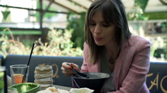 Attractive woman eating tasty soup in cafe in the garden Stock Footage