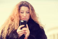 Upset skeptical unhappy woman talking texting on mobile phone Stock Photos