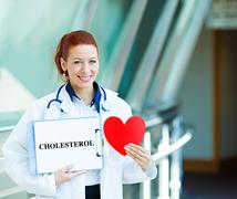 Doctor holding heart and cholesterol sign - stock photo