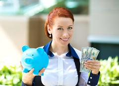 Businesswoman holding piggy bank, dollar bills - stock photo