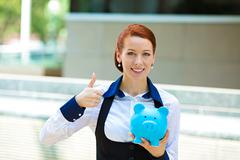 Happy woman, corporate employee holding piggy bank - stock photo