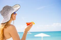 Woman in white swimsuit with cocktail on the beach enjoying sunny weather Stock Photos