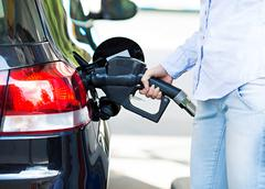 Woman at gas station, filling up her car - stock photo