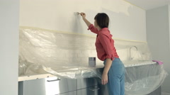 Young woman painting wall during renovation home, 4K - stock footage