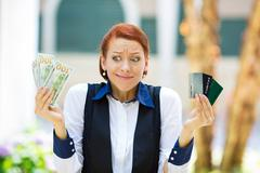 Confused woman holding credit cards and cash - stock photo