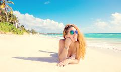 Happy young woman with sunglasses laying on beach. - stock photo