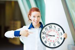 Business woman pointing on wall clock Kuvituskuvat