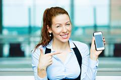 Satisfied customer pointing at her smart phone - stock photo