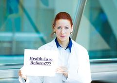 Confused doctor holding health care reform???sign - stock photo