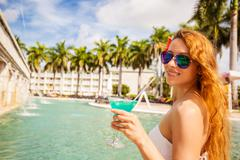 Happy woman with sunglasses holding cocktail enjoying seating by swimming poo Stock Photos
