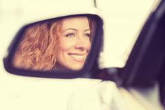 Happy woman driver reflection in car side view mirror - stock photo