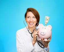 health care professional with piggy bank - stock photo