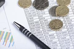 Pen and some coinage laying on a spread sheet Stock Photos