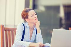 displeased worried business woman sitting in front of laptop computer - stock photo
