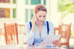 Unhappy, serious woman talking on phone holding looking at documents Stock Photos