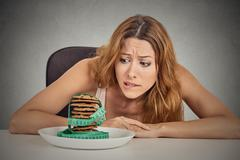 Woman craving sugar sweet cookies but worried about weight gain Stock Photos