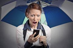 Shocked woman reading breaking news on smartphone holding umbrella Kuvituskuvat