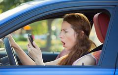 Sressed woman driver, driving in car checking smart phone - stock photo