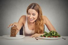 Woman deciding whether to eat healthy food or sweet cookies she craving Stock Photos