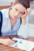 Unhappy business woman looking displeased working on financial report Stock Photos