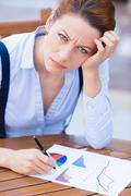 Unhappy business woman looking displeased working on financial report - stock photo