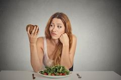 woman deciding whether to eat healthy food or sweet cookies - stock photo