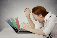 Angry businesswoman screaming at computer Stock Photos