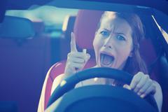 angry aggressive woman driving car - stock photo