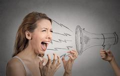 Hysterical woman shouting against someones megaphone Stock Photos