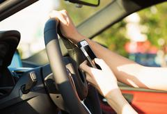 Image hands, woman sending text message on smart phone while driving to work Kuvituskuvat