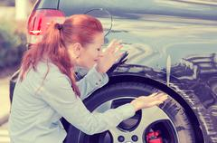 Frustrated woman checking pointing at car scratches dents - stock photo