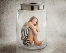 Young lonely woman sitting in glass jar Stock Photos