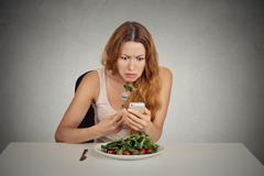Displeased girl eating green salad looking at phone seeing bad news Stock Photos