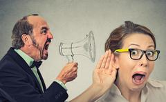 Angry man screaming in megaphone curious nosy woman listening Stock Photos