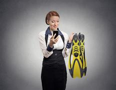 Woman looking at smartphone holding diving gear Stock Photos
