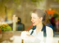 Healthy young woman enjoying her smoothie in a juice bar - stock photo