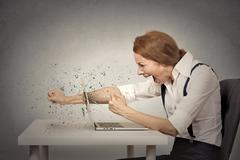 Furious businesswoman throws a punch into computer, screaming Stock Photos