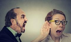 angry man screaming curious woman with hand to ear gesture listens - stock photo