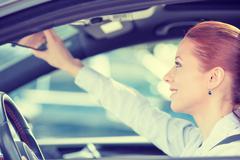 Woman driver looking adjusting rear view car mirror Stock Photos