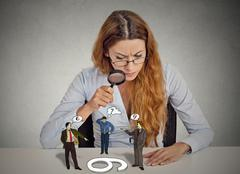 Businesswoman skeptically looking at arguing people through magnifying glass Stock Photos