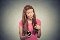 angry woman unhappy, annoyed by something on her cell phone texting - stock photo