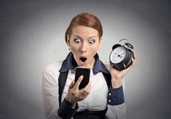 Shocked business woman with alarm clock looking at smart phone Stock Photos