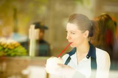 Cafe city lifestyle woman drinking coconut juice, looking outside on street t Stock Photos