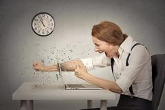 Furious businesswoman throws a punch into computer, screaming - stock photo