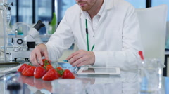 4K Food science researchers working in lab, 1 man injecting chemicals into fruit Stock Footage