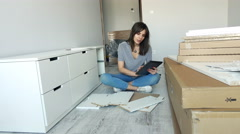 Young woman assembling furniture with tablet in her new home, 4K. Stock Footage