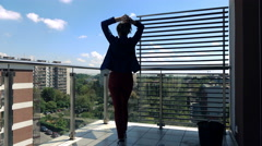 Young woman walking out on terrace with city view and stretching her arms,4K Arkistovideo