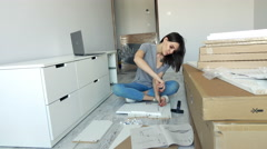 Young woman assembling furniture with screwdriver in her new home, 4K Stock Footage