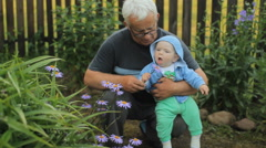 Grandfather giving a flower to his grandson. Beautiful baby smiling and touching Stock Footage