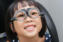 Asian Little Chinese Girl Doing Eyes Examination - stock photo